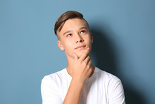 Thoughtful Teenage Boy On Color Background