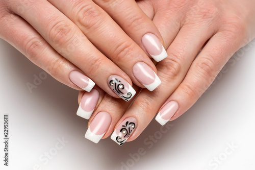 Aluminium Prints Manicure classic white French manicure with black monograms and crystals on long square nails on a white background close-up