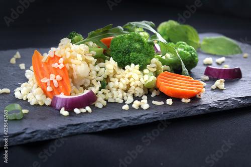 In de dag Buffet, Bar Lekka dieta, ryż z brokułami i marchewką. Ryż brązowy z warzywami podana czarnym talerzu.