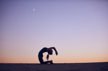 Beautiful Young Woman Practices Advanced Variation Of Camel Pose - Ustrasana In The Desert At Night