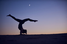 Beautiful Young Woman Practices Inverse Forearm Stand Yoga Asana Vrischikasana Scorpion Pose In The Desert At Night