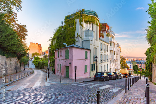 Foto op Plexiglas Historisch geb. Cozy old street with pink house at the sunny sunrise, quarter Montmartre in Paris, France