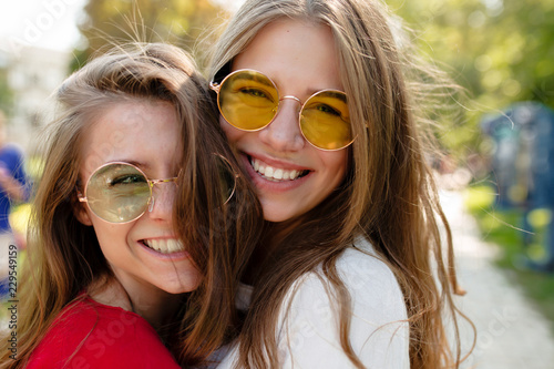 Foto  Close up outdoor portrait of two cheerful female best friends in bright glasses smilimg and posing at camera in sunny park