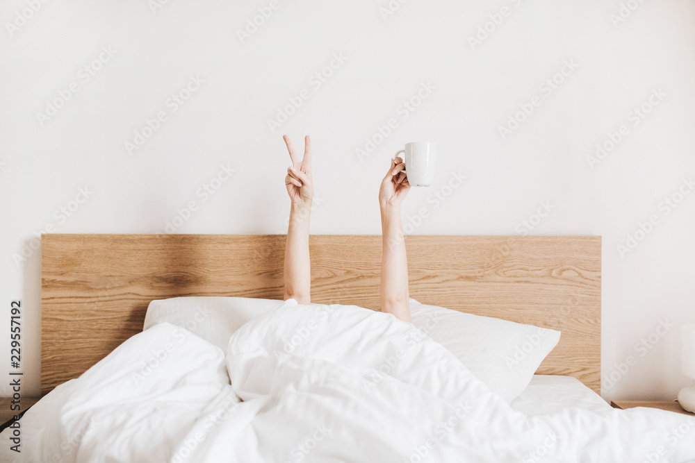 Fototapety, obrazy: Hand's of young woman with coffee mug in bed with white linens. Minimal happy morning concept.