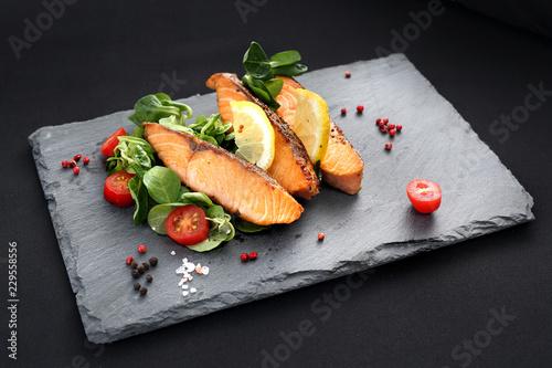 Kawałki pieczonego łososia na sałacie. Danie obiadowe na czarnym talerzu.