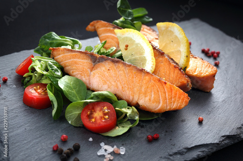 Fototapeta Grillowany łosoś na sałacie.Danie obiadowe na czarnym talerzu. obraz