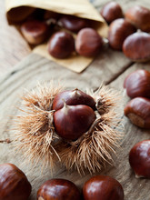 Roasted On The Open Fire Sweet Chestnut Nuts On Wooden Rustic Natural Background. Perfect Traditional Meal For Christmas Or Street Food.