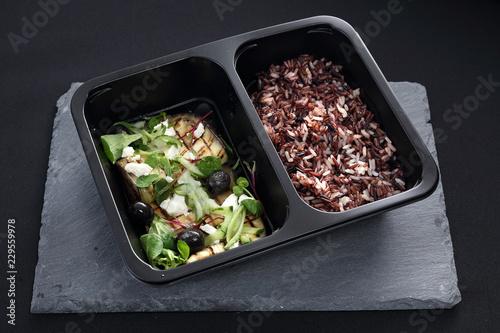 Potrawa w pojemniku. Grillowany bakłażan z czarnymi oliwkami, serem feta i zielonymi warzywami podany z dzikim ryżem
