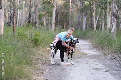 Young girl hugging a dalmatian puppy on a bush track in Australia Tapéta, Fotótapéta