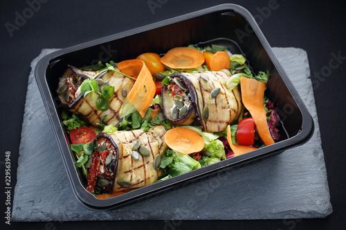 Fototapeta Dieta pudełkowa. Roladki z grillowanego bakłażana z suszonymi pomidorami i serem podane na sałacie i marchewce zapakowane w pojemnik na żywność. obraz