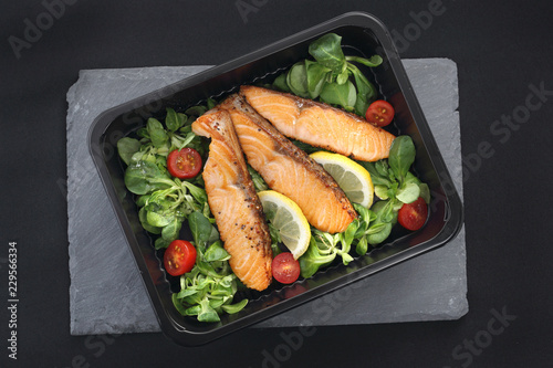 Kawałki pieczonego łososia na sałacie. Gotowe danie na wynos zapakowane w lunch box.