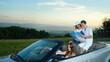 Company traveling by car, couple sitting on cabriolet and holding map.