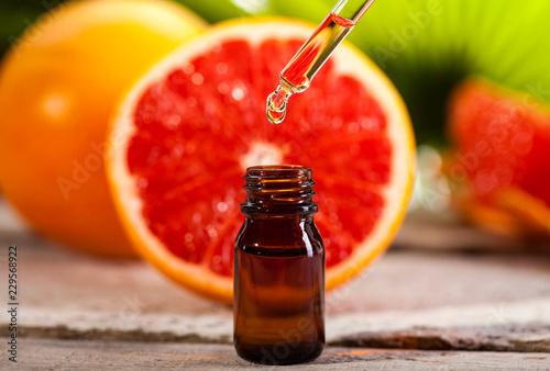 Fototapeta Grapefruit Essential Oil on green leaves background