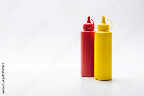 Fotografie, Obraz close-up shot of bottles of ketchup and mustard on white surface