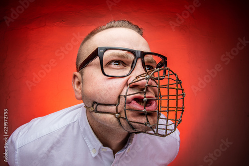 Leinwand Poster  Angry and agressive man with dog muzzle basket shouting