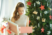 Unhappy Woman With Opened Christmas Gift Near Christmas Tree