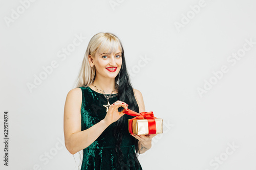 Fényképezés Portrait of a young blonde woman unwrapping golden gift with red bow
