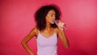 Attractive african-american sporty young woman drinking bottle of water on pink wall background. Girl in sports clothes after fitness. Studio footage. 4k