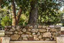 Stone Bench Under Tree In Outdoor Park Environment, South Country In Mediterranean District And Warm Weather