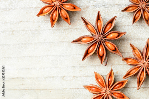 Fototapeta star anise fruits on the wooden board, top view obraz