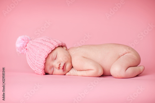 Fototapeta Newborn Baby Girl in Knit Hat, Isolated on Pink obraz