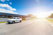 Abstract blur and bokeh. White Luxury car in racetrack and speed racing back ground clear sky. Sunlight and flare concept.