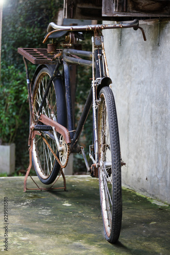 Deurstickers Fiets Vintage bicycle leaning on raw cement wall.