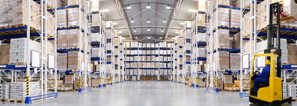 Fototapeta Huge distribution warehouse with high shelves and forklift