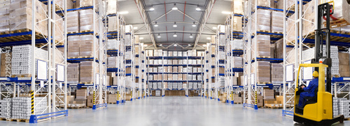 Photo Huge distribution warehouse with high shelves and forklift