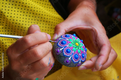 Drawing with a brush a mandala on a stone Fototapet