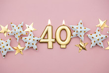 Number 40 Gold Candle And Stars On A Pastel Pink Background