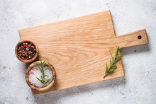 Wooden Cutting Board With Sea Salt And Pepper On White Stone Tab