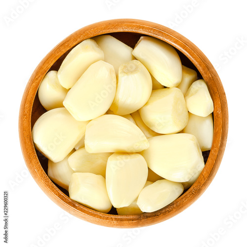 Peeled garlic cloves in wooden bowl. Allium sativum, with its pungent flavor is used as a seasoning or condiment and also in medicine. Isolated macro food photo closeup from above on white background.
