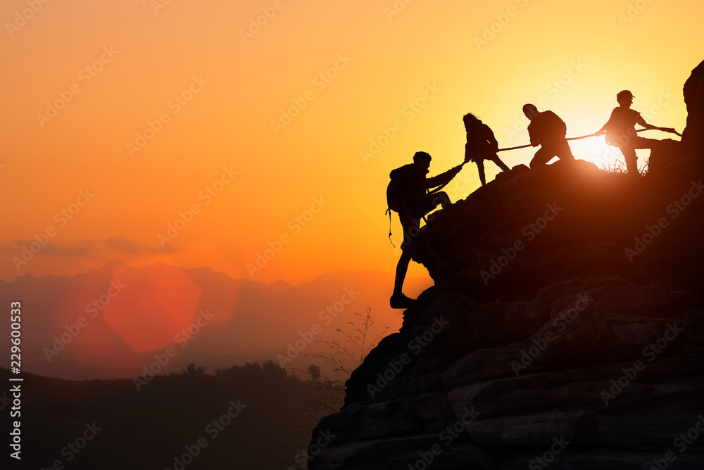 Fototapeta Silhouette of the climbing team helping each other while climbing up in a sunset. The concept of aid.
