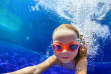 Happy Family In Swimming Pool. Smiling Child In Goggles Swim, Dive In Pool With Fun - Jump Deep Down Underwater. Healthy Lifestyle, People Water Sport Activity, Swimming Lessons On Holidays With Kids
