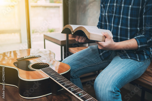 close up of a man hands holding  and read book  with guitar on wooden table, chr Wallpaper Mural