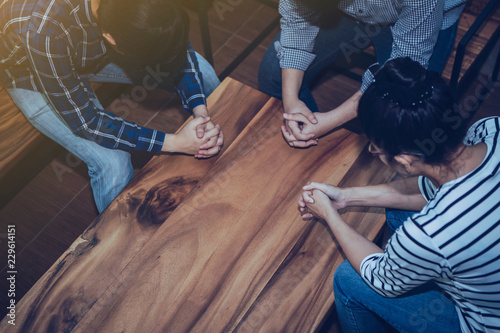 Christian people prays together around wooden table Fototapete