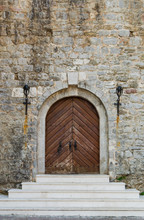 Old Wooden Doors Of An Old Castle With A White Staircase And A Stone Wall.