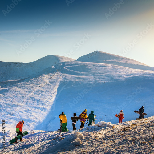 Young people in a mountain are ready to ride on snowboards. Group of snowboarders in Carpathian mountains.