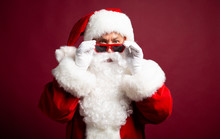 Surprised Santa Clause Wearing Sunglasses And Looking At Camera On Red Background