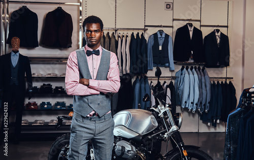 eb5ed8b2 Elegantly dressed African American young man posing with crossed arms near  retro sports motorbike at the