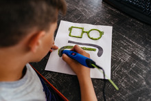 Teenager Boy Draws Different Things By 3d Pen With A Blue Plastic Handle. Mathematics. Engineering. Technology. Robotics. STEM Education.