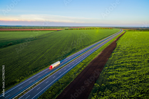 Dump trucks carrying goods on the highway. Red truck driving on asphalt road along the green fields. seen from the air. Aerial view landscape. drone photography.  cargo delivery