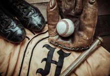 A Group Of Vintage Baseball Equipment, Bats, Gloves, Baseballsand A Jersey On Wooden Background