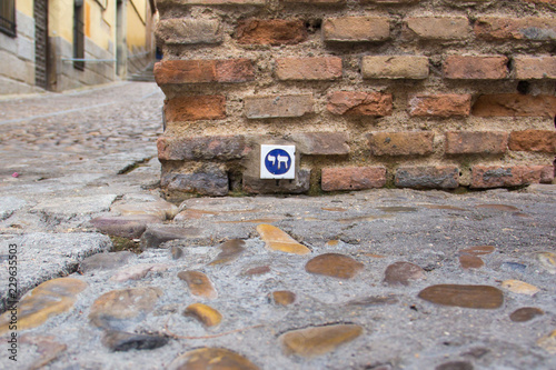 """A blue and white pottery tile with the Chai symbol meaning """"alive"""" in Hebrew, in a brick wall in the Jewish Quarter of Toledo, Castilla-La Mancha, Spain, a UNESCO World Heritage Site"""