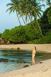Girl in swimsuit walks on a tropical beach