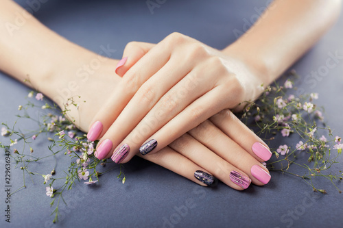Poster Manicure Pink and black manicure with flowers on grey background. Nail art