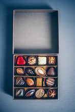An Open Small Box Of Chocolate Pralines And Truffles Assorted. Blue Toned Background, Directly Above.