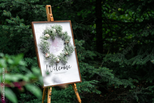 Cuadros en Lienzo Blank signpost pointer on a wooden easel in a frame with a wreath