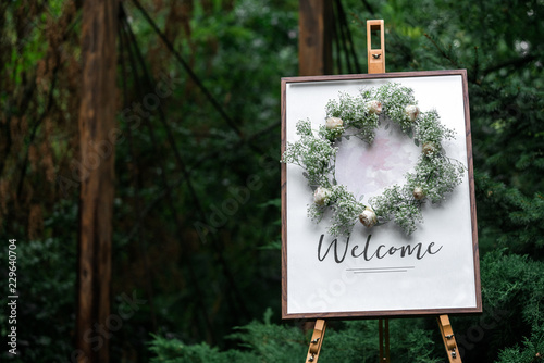 The easel is wooden with a frame plate and the words welcome Fototapet